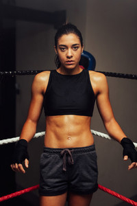 Female athlete stands in one corner of boxing ring