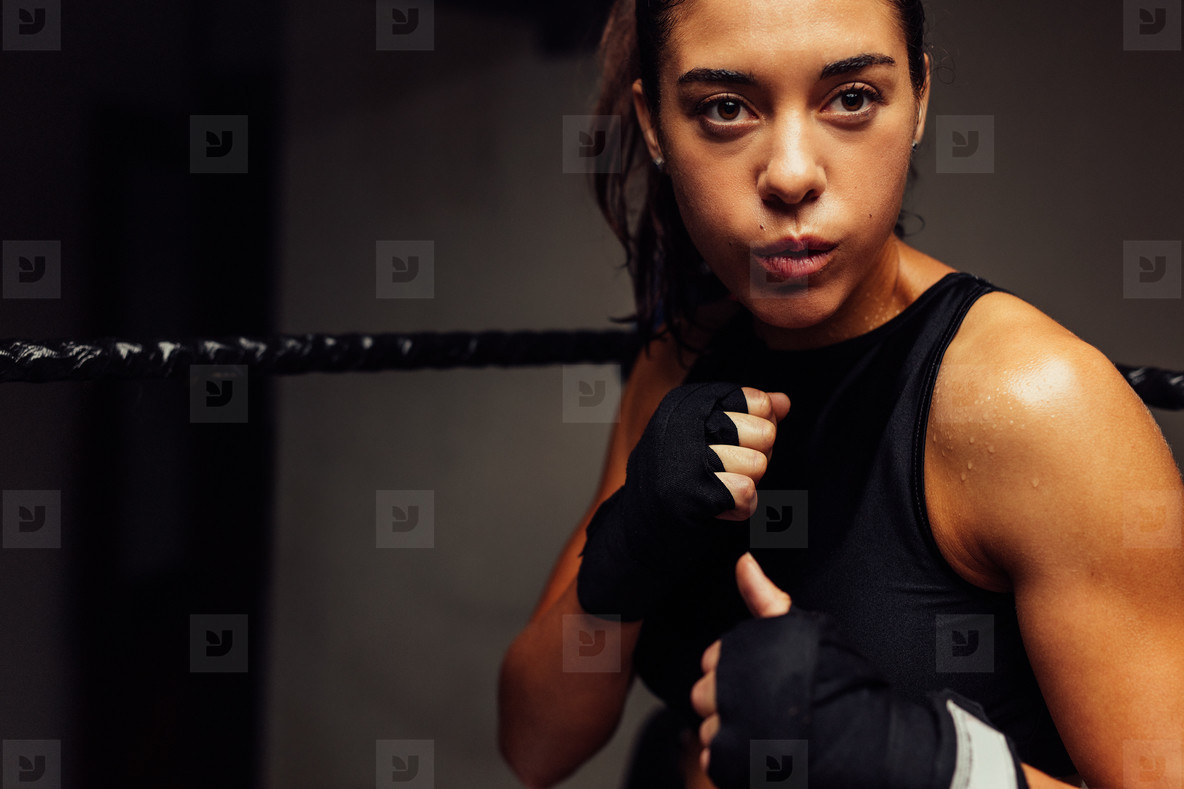 Woman in boxing ring with wrapped hands