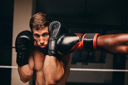 Boxing athlete blocking a punch to jaw