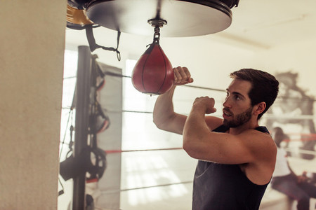 Young man working out with speed bag