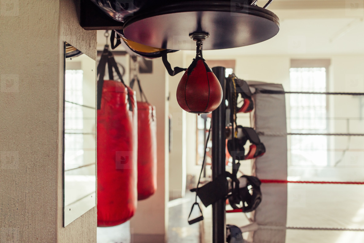 Small red punching bag hangs near other equipment