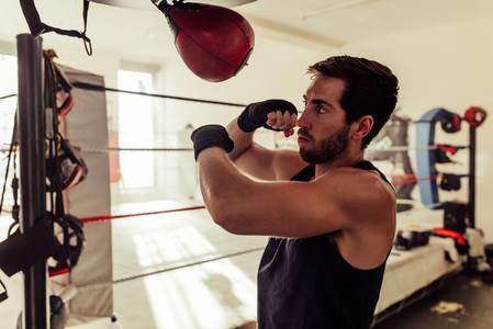 Handsome boxer with beard strikes punching bag