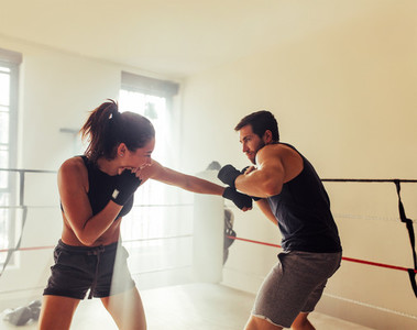 Male and female athletes sparring in boxing ring