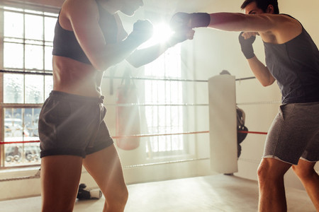 Male and female pugilists fighting in boxing ring