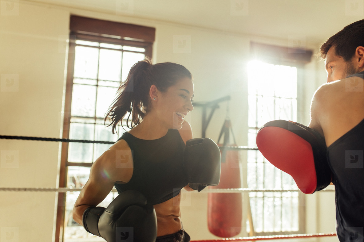Happy female boxer sparring with instructor