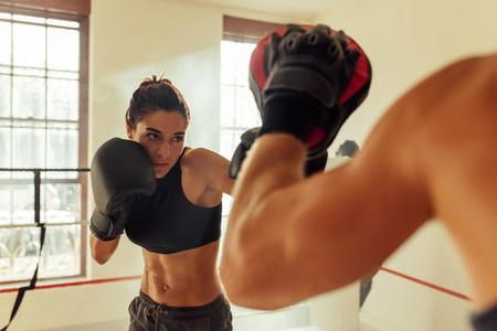 Muscular female pugilist throws a punch
