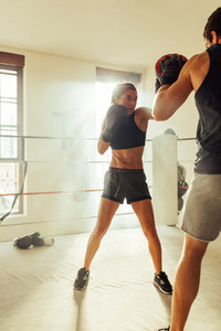 Beautiful pugilist sparring with partner in gym