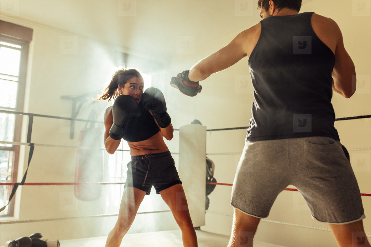 Young female boxer steps back as opponent strikes