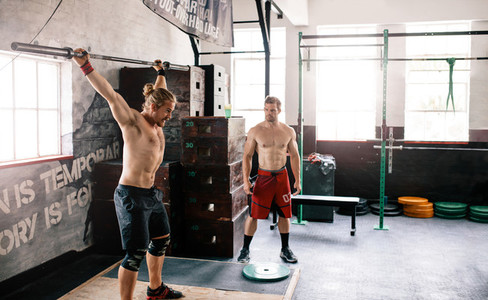 Two male athlete exercising at the gym