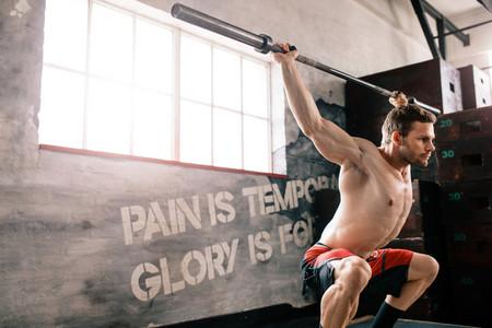 Young man at crossfit gym lifting barbell