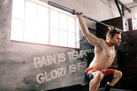 Young man at crossfit gym lifting barbell