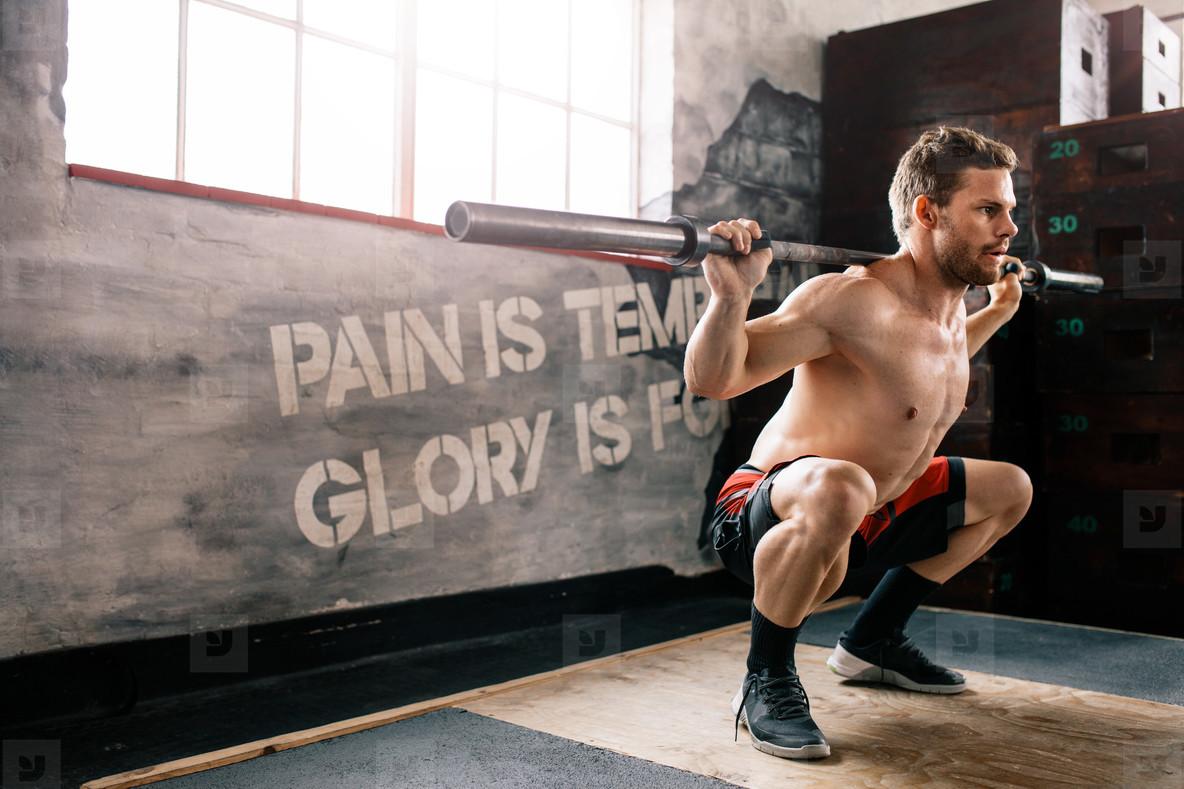 Muscular man at crossfit gym lifting barbell