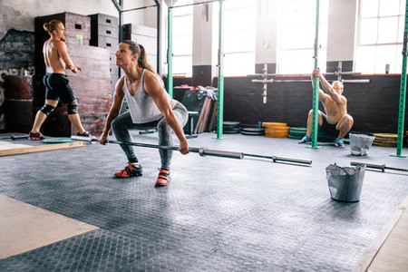 Fit people exercising in crossfit gym