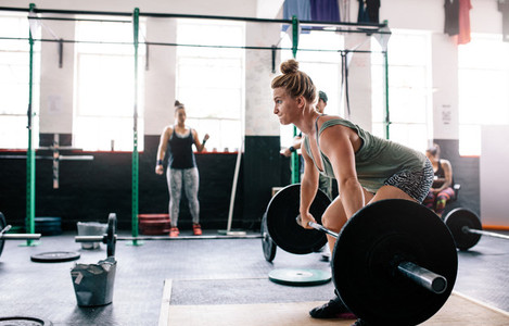 Muscular woman weight lifting at crossfit gym