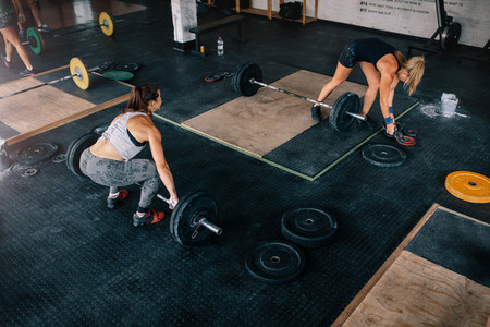 Muscular women exercising with heavy weights in gym