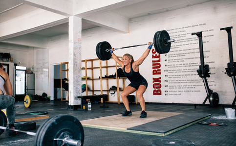 Female performing deadlift exercise with barbell
