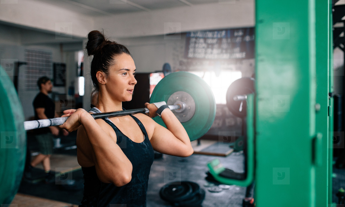 Woman doing squats with barbell in a gym