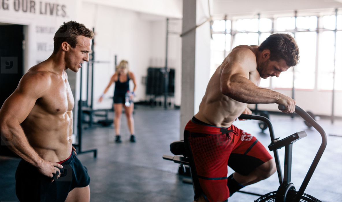 Fitness man exercising in gym with coach