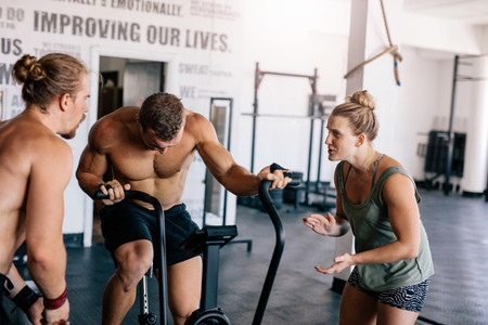 Man doing  intense workout on gym bike with personal coach
