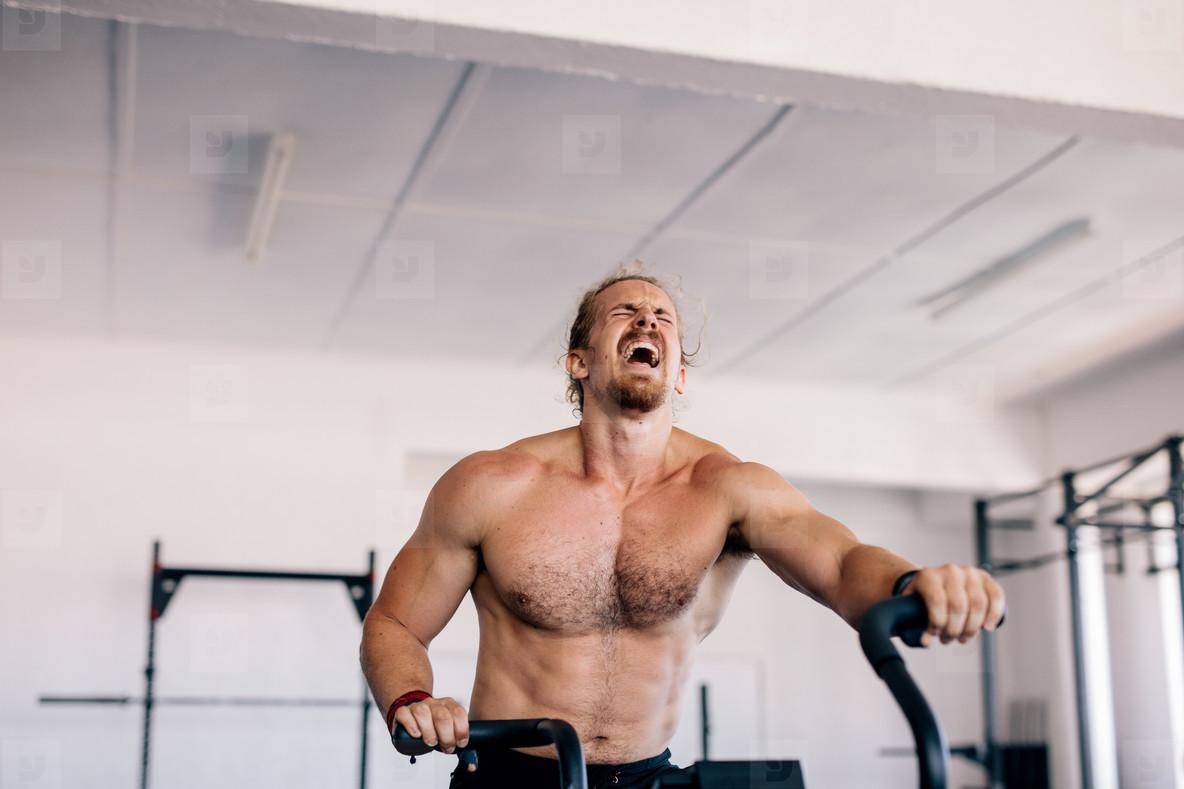 Muscular man doing intense workout on gym bike