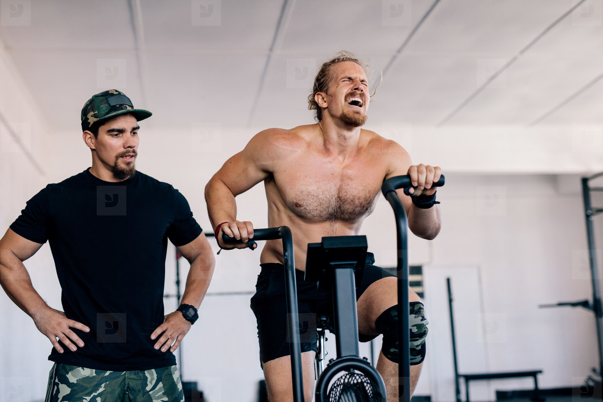 Bodybuilder spinning stationary bike in gym with personal traine