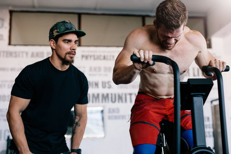 Fitness instructor with man workout on exercise bike