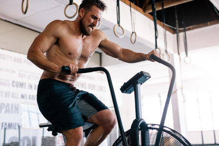 Strong man riding on exercise bike in gym