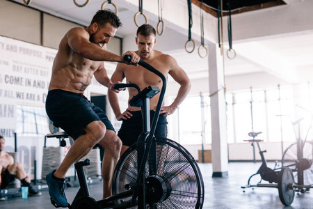 Muscular man cycling in a gym with personal trainer