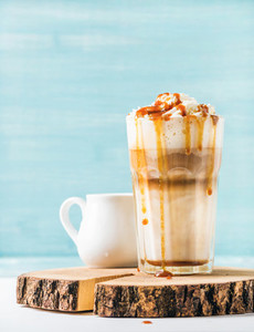 Latte macchiato with whipped cream and caramel sauce in tall glass on wooden board over blue painted wall background  copy space