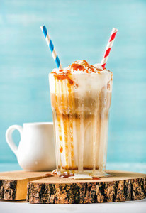 Latte macchiato with whipped cream and caramel sauce in tall glass on wooden board over blue painted wall background