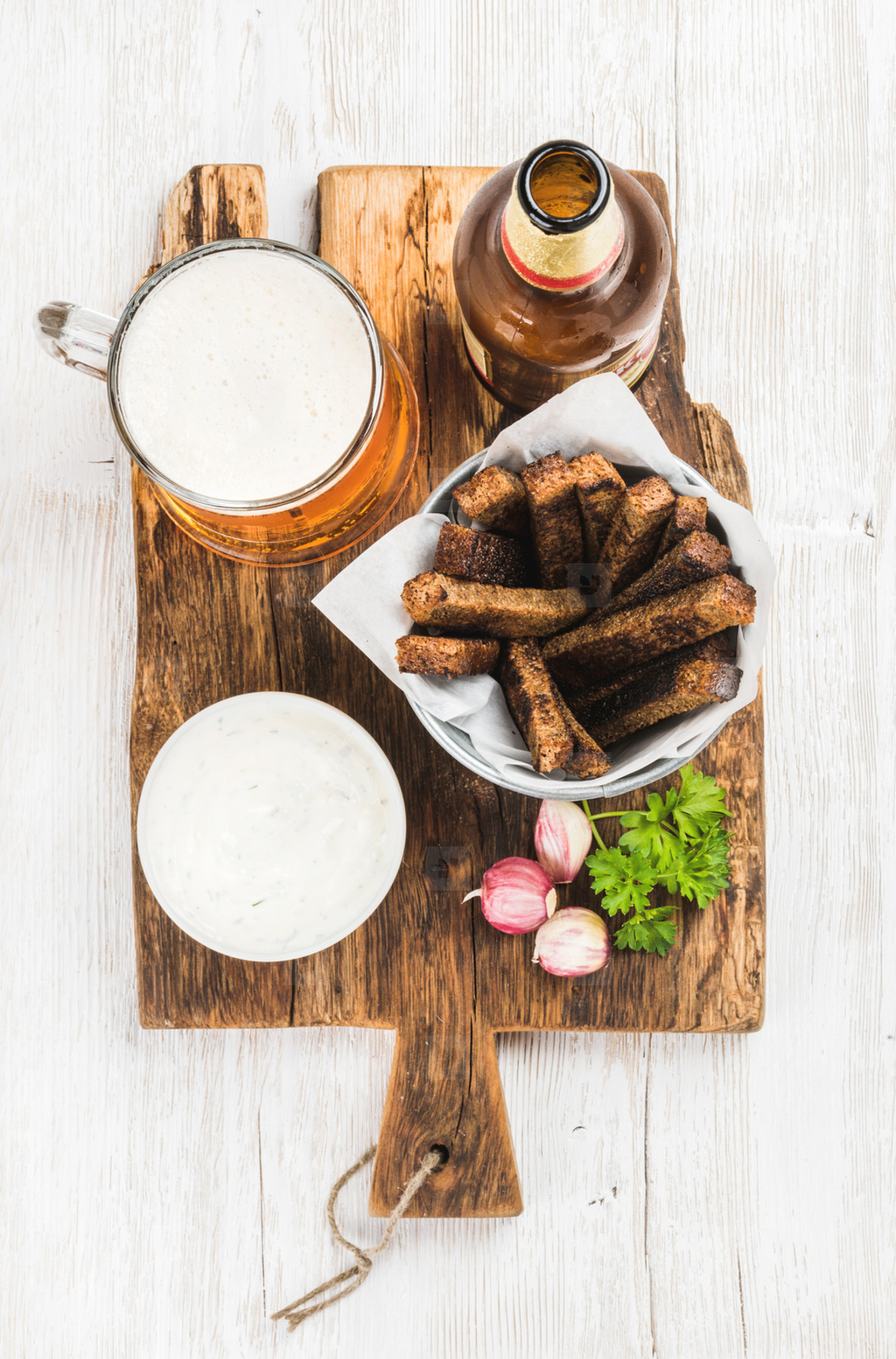 Beer snack set  Pint of pilsener in mug  open glass  bottle  rye bread croutons with garlic cream cheese sauce on rustic wooden board over white painted old  background