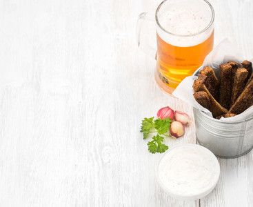 Beer snack set Pint of pilsener in mug and rye bread croutons with garlic cream cheese sauce over white painted old wooden background selective focus