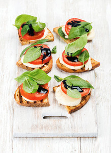 Caprese sandwiches with tomato mozzarella cheese basil and balsamic glaze on white painted board over light wooden background