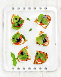 Caprese sandwiches with tomato mozzarella cheese basil and balsamic glaze on white baking tray over light wooden background