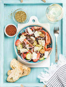 Greek salad with bread oregano pepper and glass of wine