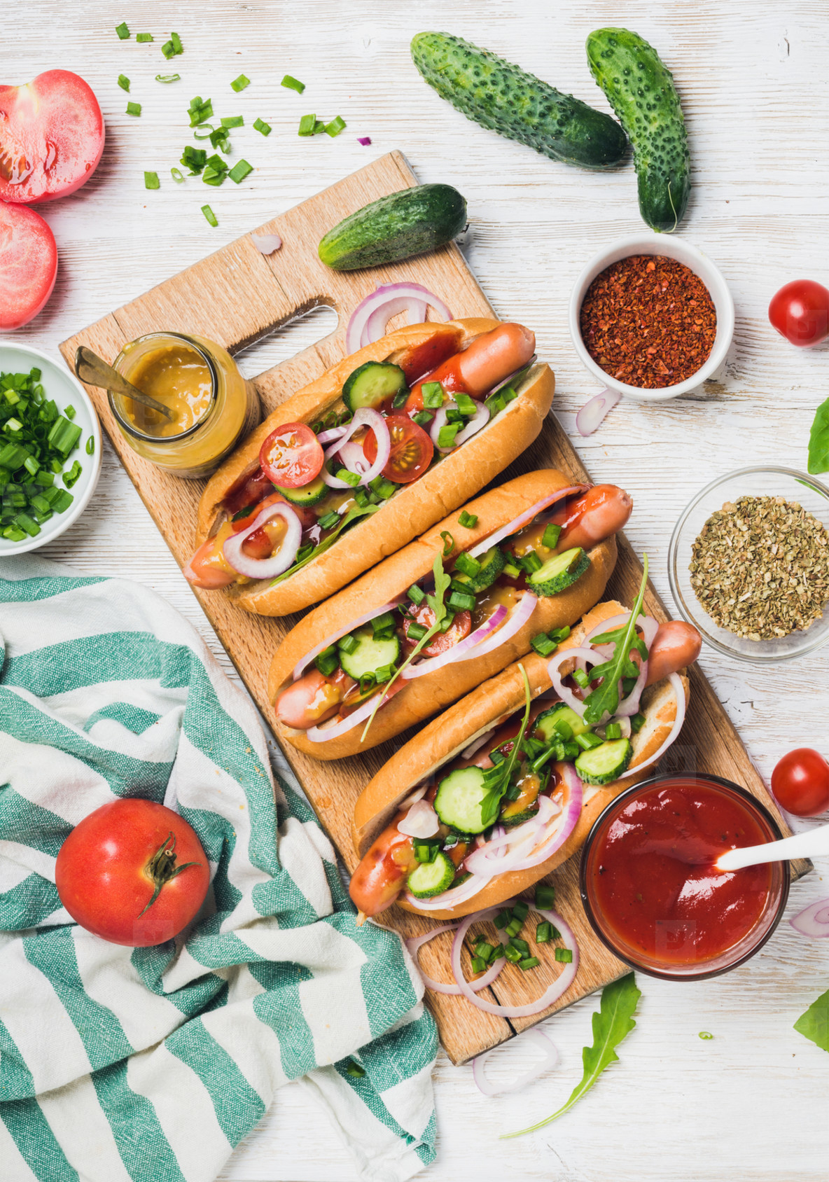 Homemade hot dogs with fresh vegetables and spices over white background