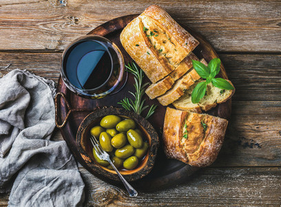 Red wine glass  green olives and ciabatta over wooden background