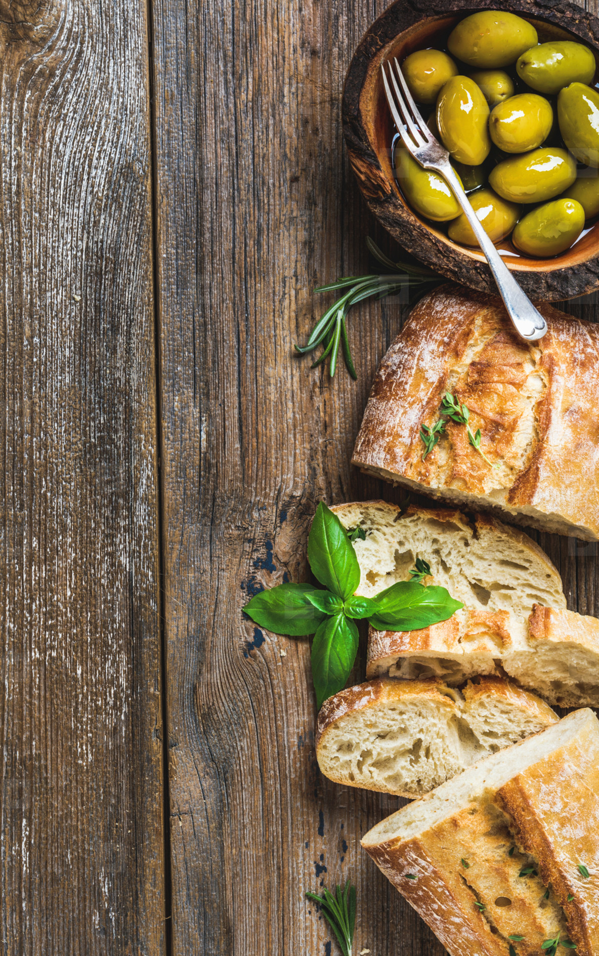Green olives and slices of ciabatta over rustic wooden background