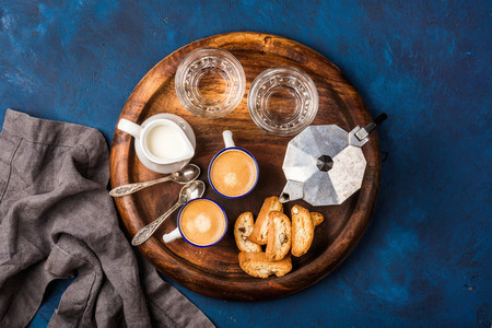 Coffee espresso  cantucci  cookies  milk and water on wooden board