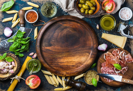 Italian food cooking ingredients on dark plywood background  copy space