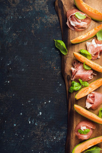 Prosciutto with cantaloupe melon and basil leaves on wooden board