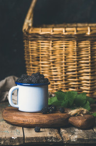 Blackberries in white cup on wooden board over rustic table
