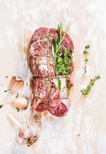 Raw uncooked roastbeef meat cut with rosemary  thyme and garlic
