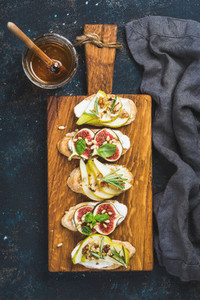 Crostini with fruits  cheese and herbs on rustic wooden board