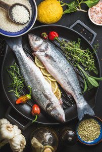 Ingredients for cooking healthy fish dinner  Raw uncooked seabass with rice  lemon  herbs and spices on black grilling iron pan over dark background