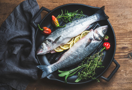 Raw uncooked seabass fish with lemon slices  herbs and spices on black grilling iron pan over rustic wooden background