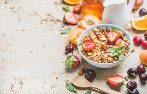Healthy breakfast ingredients  Bowl of oat granola with milk  fresh fruit  berries and honey