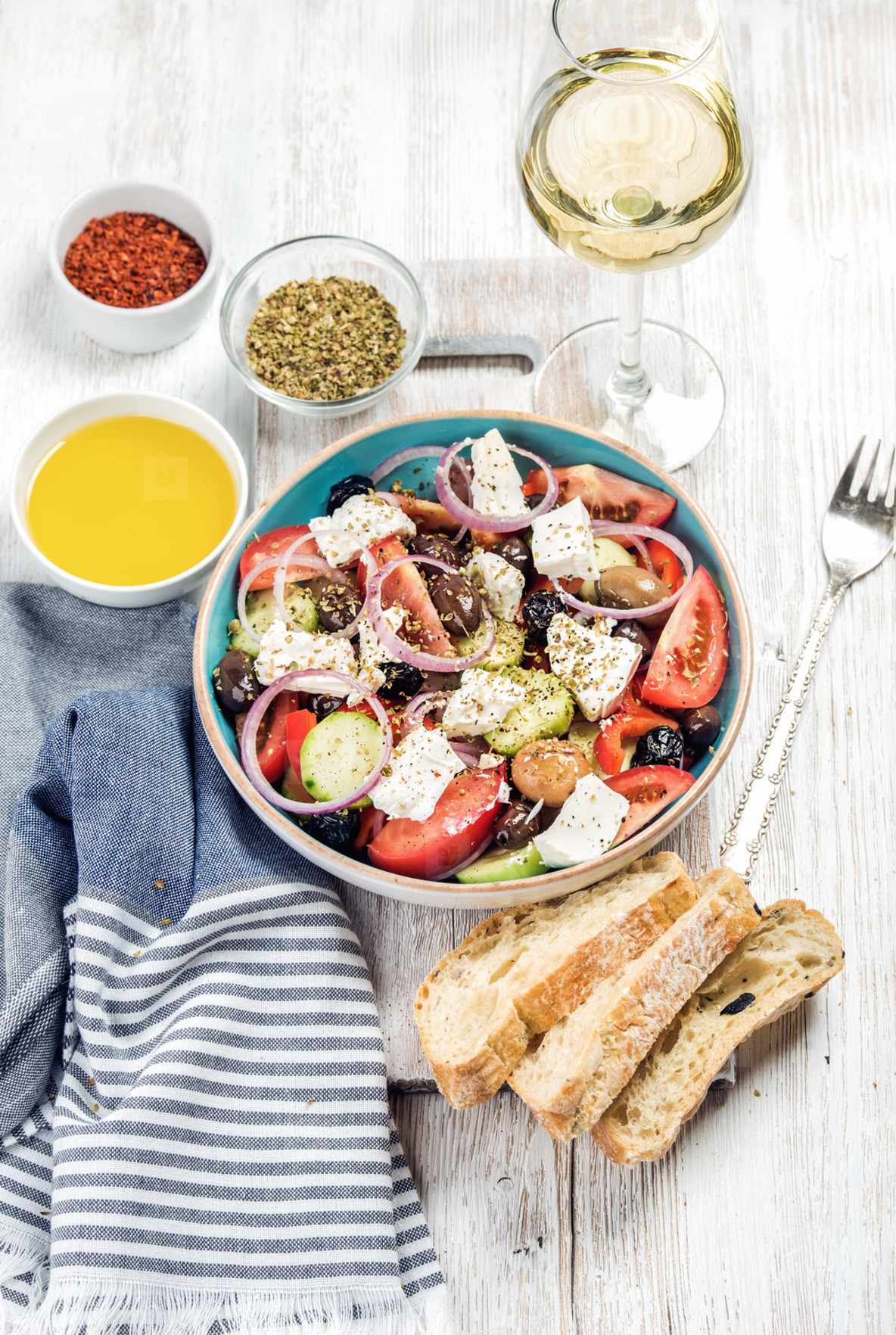 Greek salad with olive oil  bread slices  spices  white wine