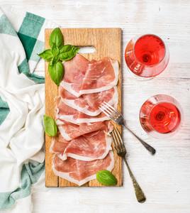 Prosciutto di Parma ham slices and rose wine glasses