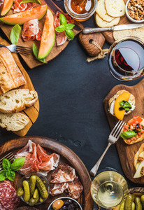 Italian antipasti wine snacks set over black grunge background